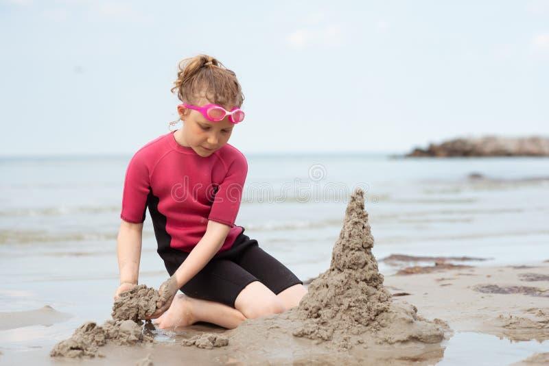 使用与沙子的氯丁胶泳装的俏丽的女孩在海 图库摄影