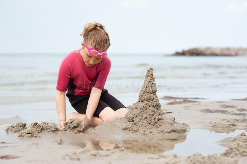 使用与沙子的氯丁胶泳装的俏丽的女孩在海 免版税库存照片