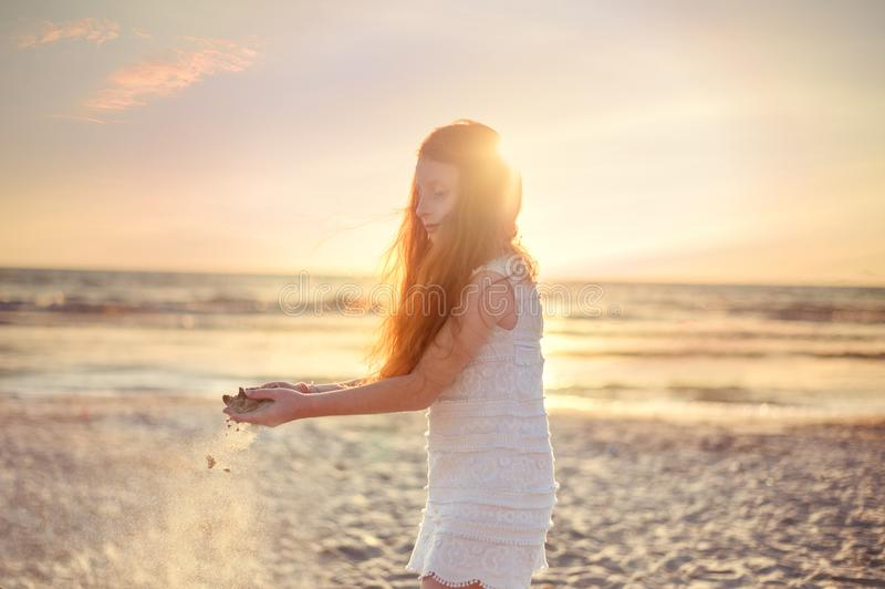 使用与沙子,在亚得里亚海海滩的日落天空的小女孩在阿尔巴尼亚 滑倒通过手指的沙子 背景概念查出的目的程序时间白色 免版税库存照片