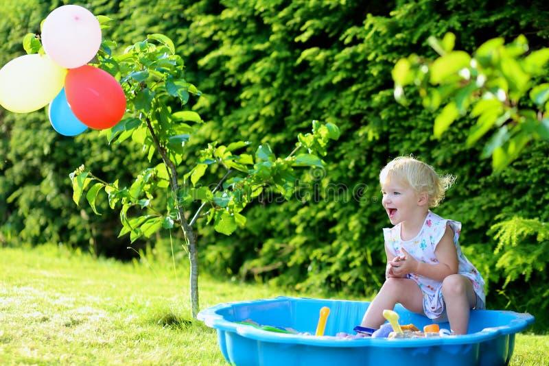 使用与沙盒的小女孩在庭院里 免版税库存照片