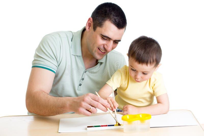 使用与油漆颜色的父亲和孩子 免版税库存照片