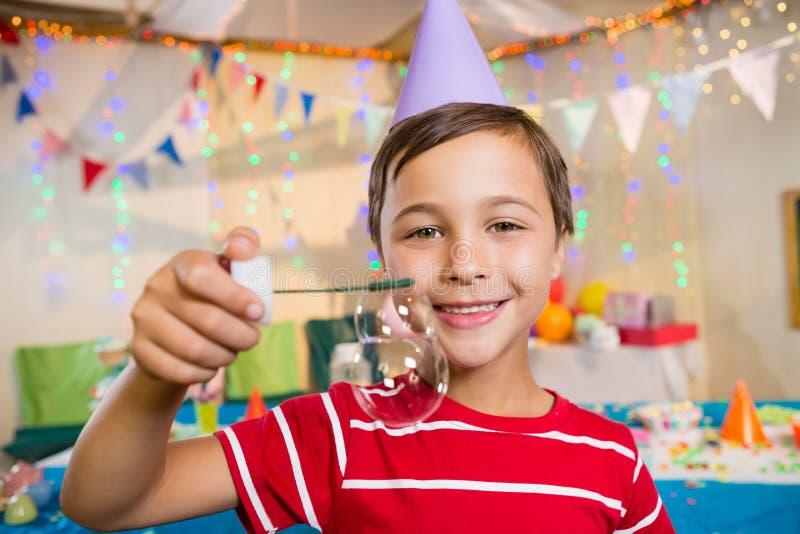 使用与泡影鞭子的逗人喜爱的男孩在生日聚会期间 免版税库存照片