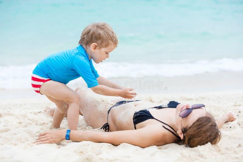 使用与海滩的母亲的逗人喜爱的小男孩 库存照片
