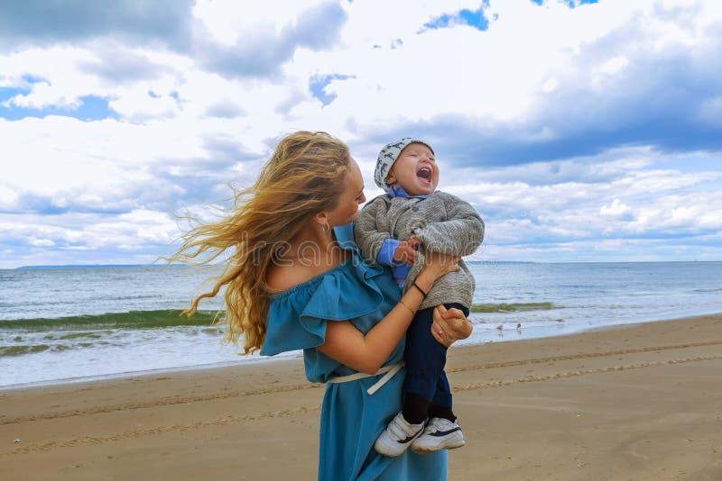 使用与海滩的年轻儿子的愉快的家庭母亲 库存照片