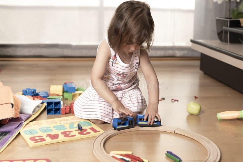 使用与火车玩具的女孩 免版税库存图片