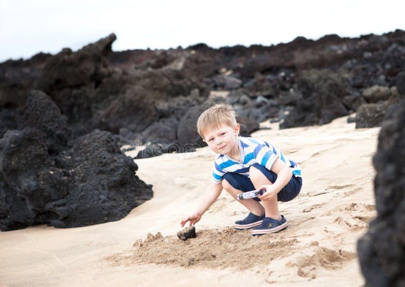 使用与熔岩岩石的逗人喜爱的小男孩 免版税库存图片