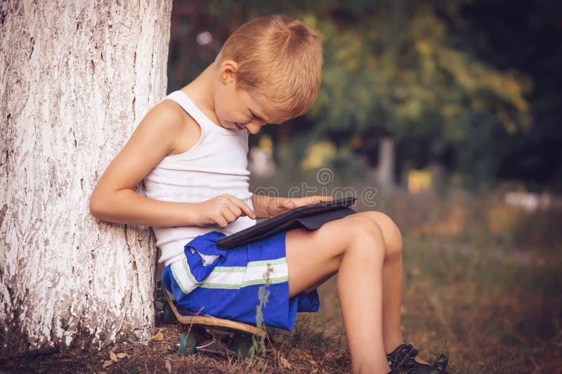 使用与片剂个人计算机的男孩孩子室外 库存照片