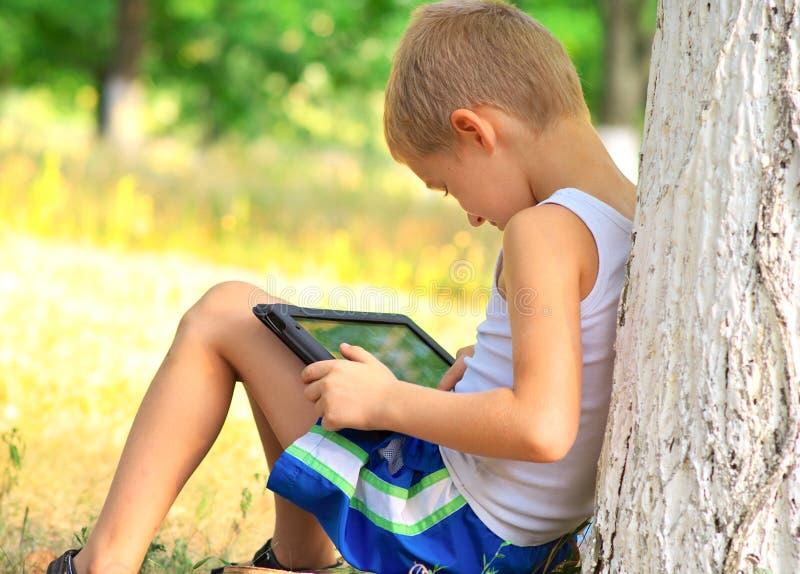使用与片剂个人计算机的男孩孩子 免版税库存照片