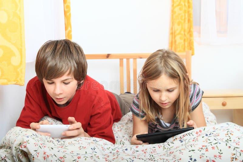 使用与片剂和智能手机的孩子 库存照片