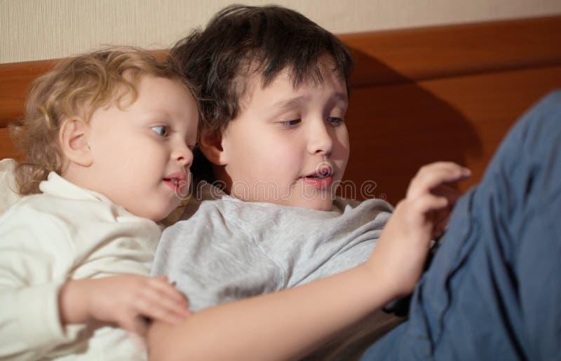 使用与片剂的两个幼儿 免版税库存照片
