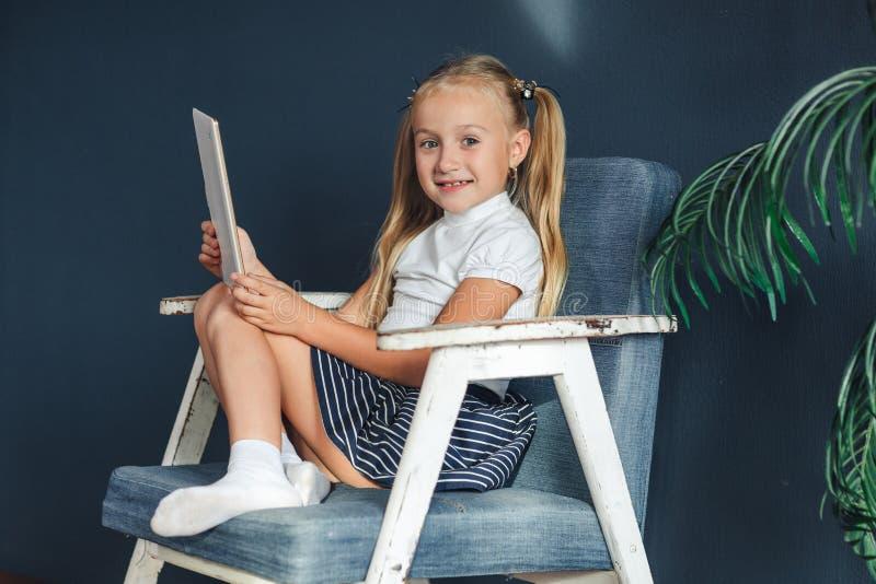使用与片剂的逗人喜爱的女孩 愉快的blondy女孩在家 滑稽的可爱的女孩获得乐趣在孩子屋子里 免版税库存照片