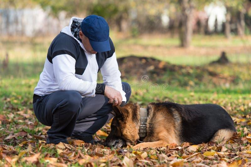 成人片人与兽交配_download 使用与狗德国牧羊犬的人在公园 库存照片.