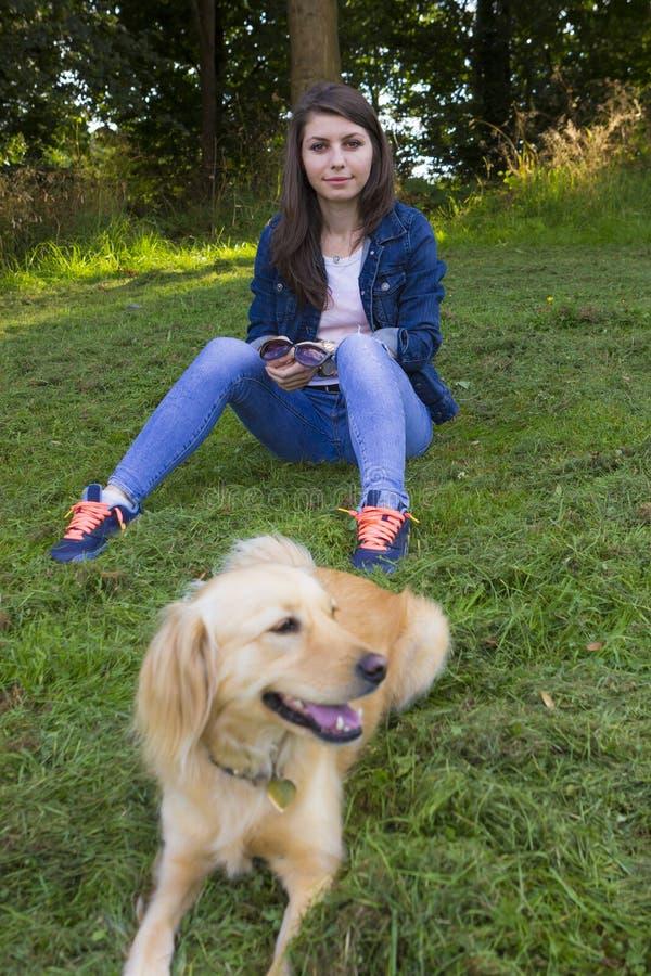 使用与狗的女孩在夏日 库存照片