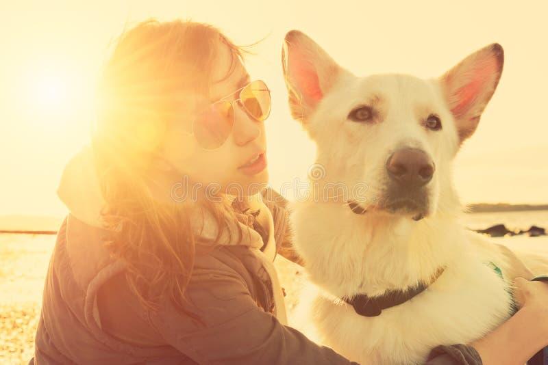 使用与狗的行家女孩在海滩在日落,强的透镜火光作用期间 免版税库存图片