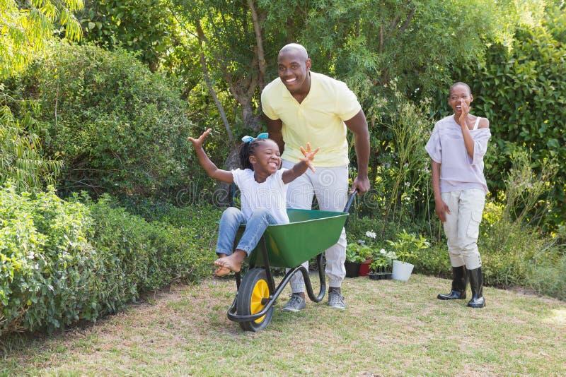 使用与独轮车和他们的女儿的愉快的微笑的夫妇 免版税图库摄影