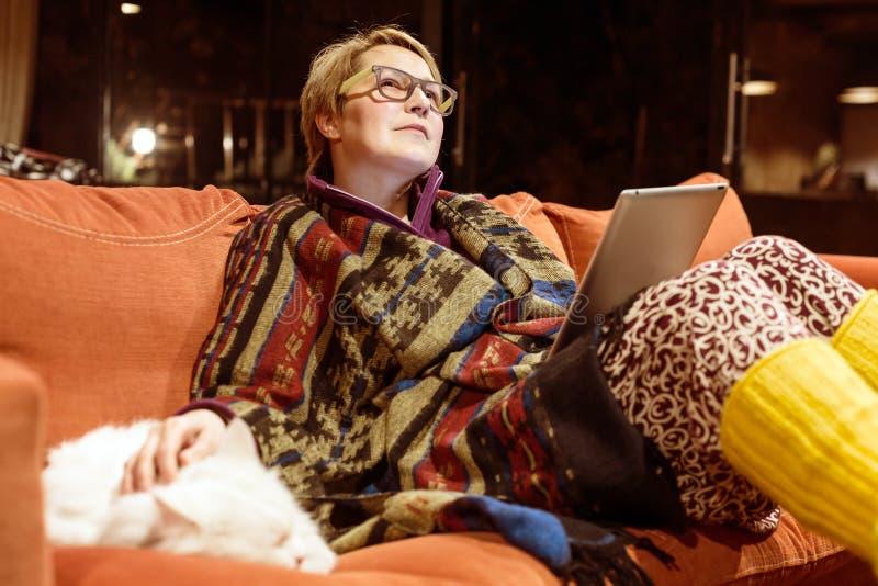 使用与猫的舒适家庭内部沉思妇女读书片剂 免版税库存图片
