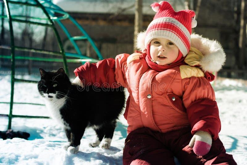 使用与猫的滑稽的愉快的孩子。 库存图片