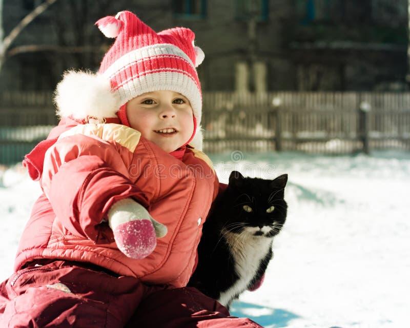使用与猫的滑稽的愉快的孩子。 免版税库存照片