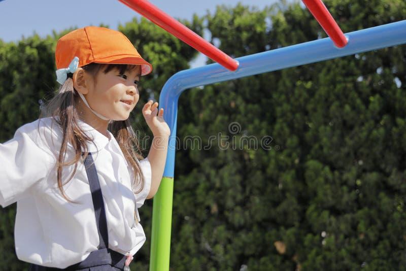 使用与猴子栏杆的校服的日本女孩 图库摄影