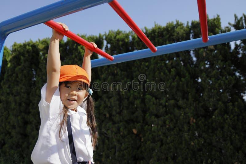 使用与猴子栏杆的校服的日本女孩 免版税库存照片