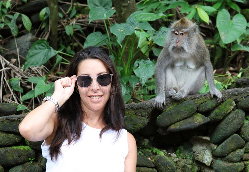 使用与猴子的美丽的女孩在猴子森林在巴厘岛印度尼西亚,有野生动物的俏丽的妇女 库存图片