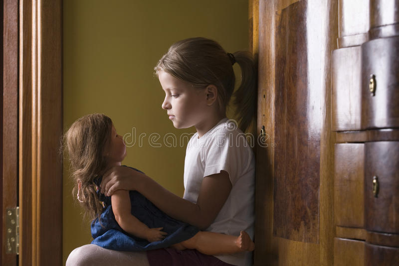 使用与玩偶的女孩在家 库存照片