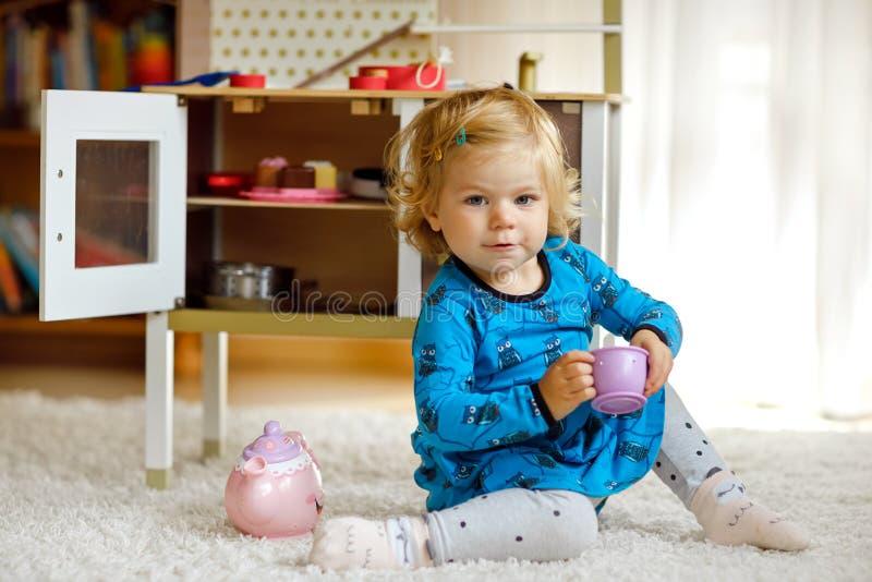 使用与玩具厨房愉快的健康小孩子的可爱的逗人喜爱的矮小的小孩女孩获得与角色比赛的乐趣,使用 图库摄影