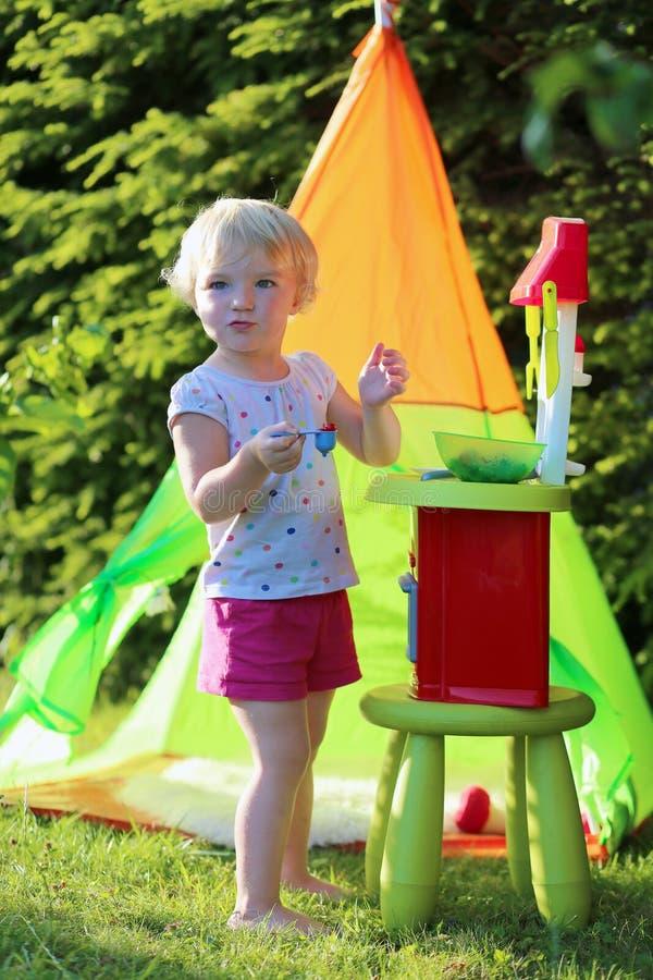 使用与玩具厨房的小女孩户外 图库摄影