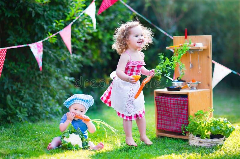 使用与玩具厨房的美丽的小孩在庭院里 库存照片