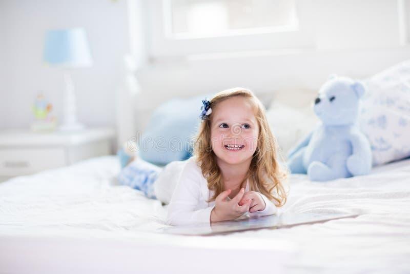 使用与玩具和在床上的小女孩读一本书 库存图片