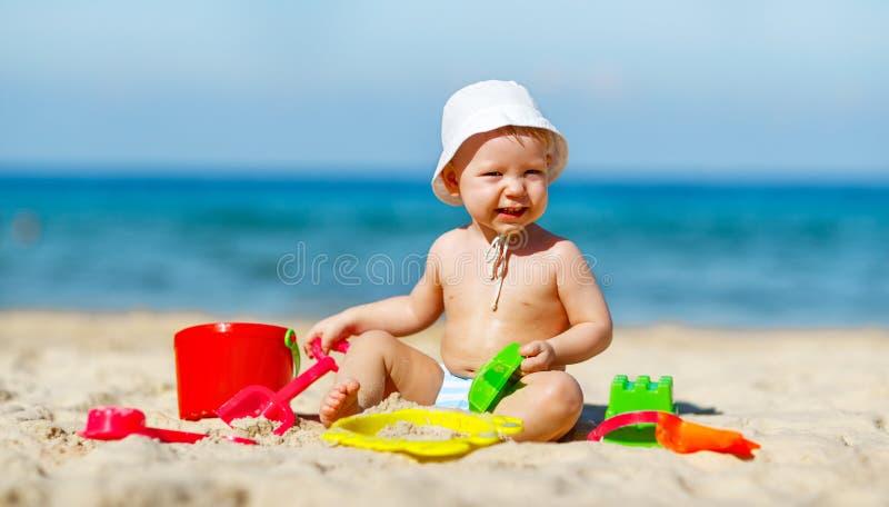 使用与玩具和沙子的男婴在海滩 免版税库存图片