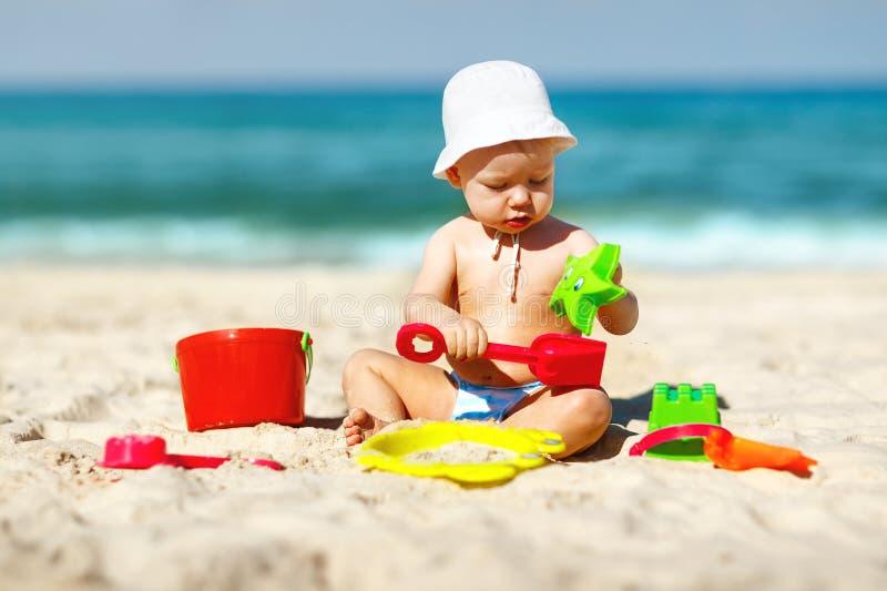 使用与玩具和沙子的男婴在海滩 库存照片