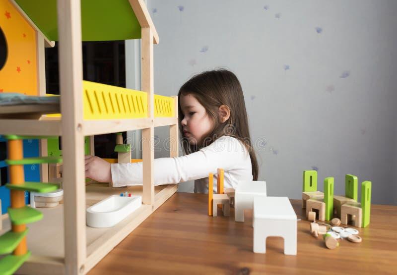 使用与玩具屋的一个小女孩 免版税库存照片