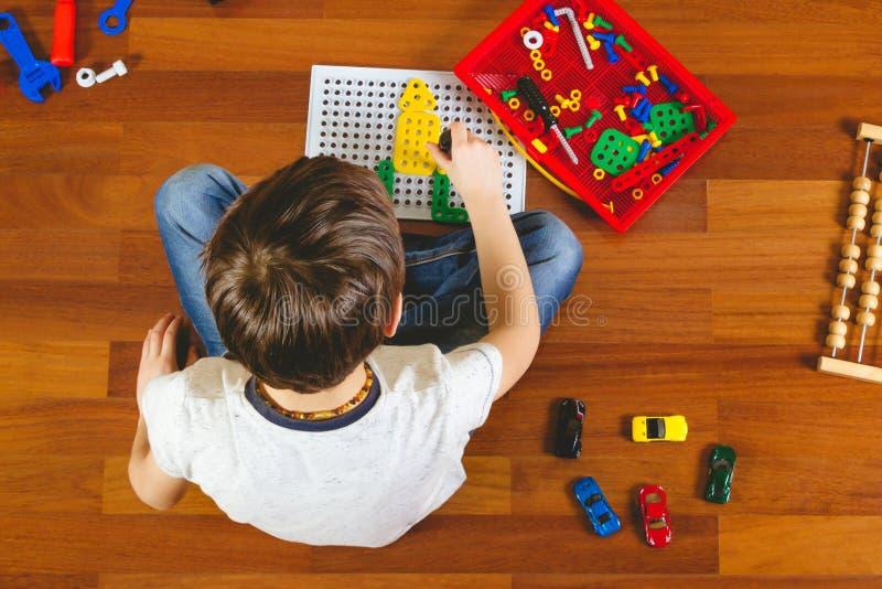 使用与玩具工具箱的孩子,当坐地板在他的屋子里时 顶视图 免版税库存照片