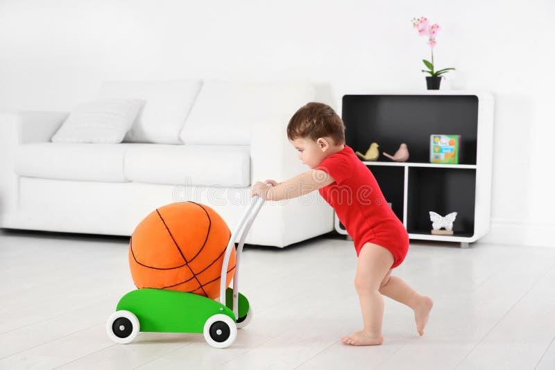 使用与玩具步行者和球的逗人喜爱的婴孩 免版税库存图片