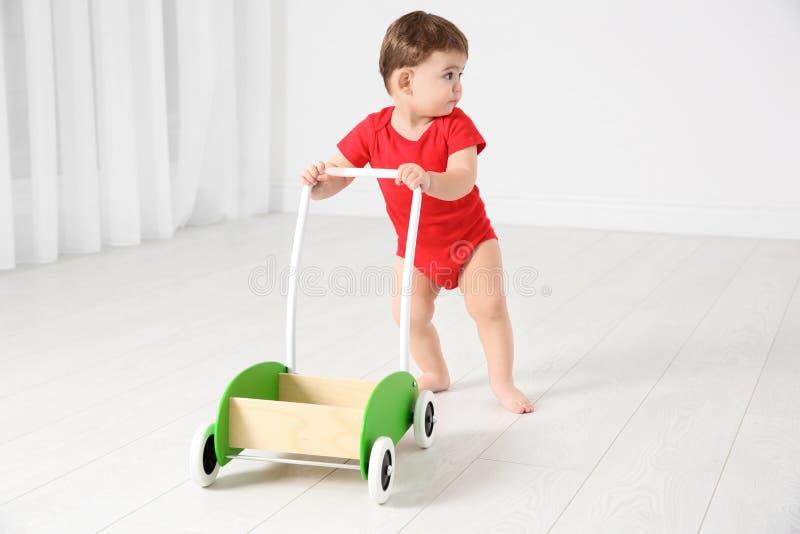 使用与玩具步行者的逗人喜爱的婴孩, 免版税库存图片