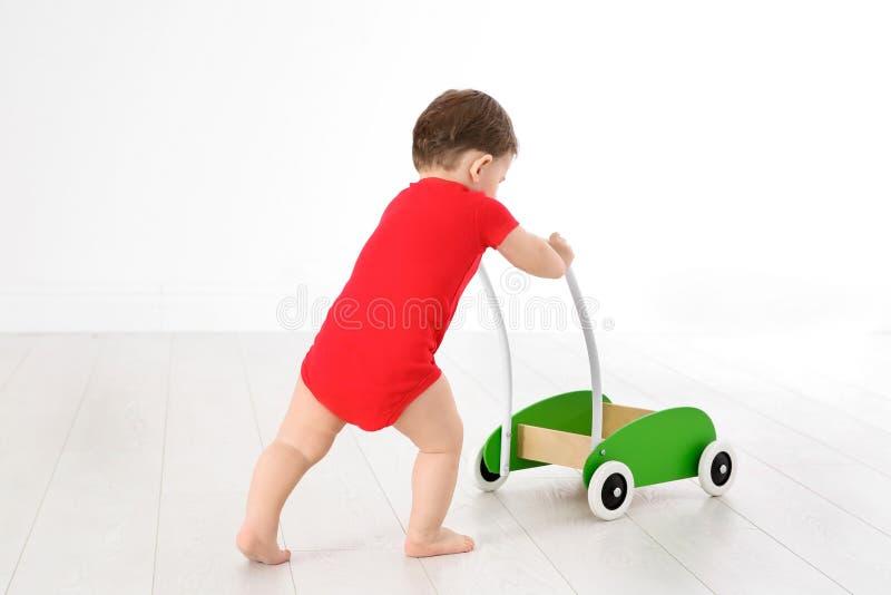 使用与玩具步行者的逗人喜爱的婴孩, 免版税图库摄影