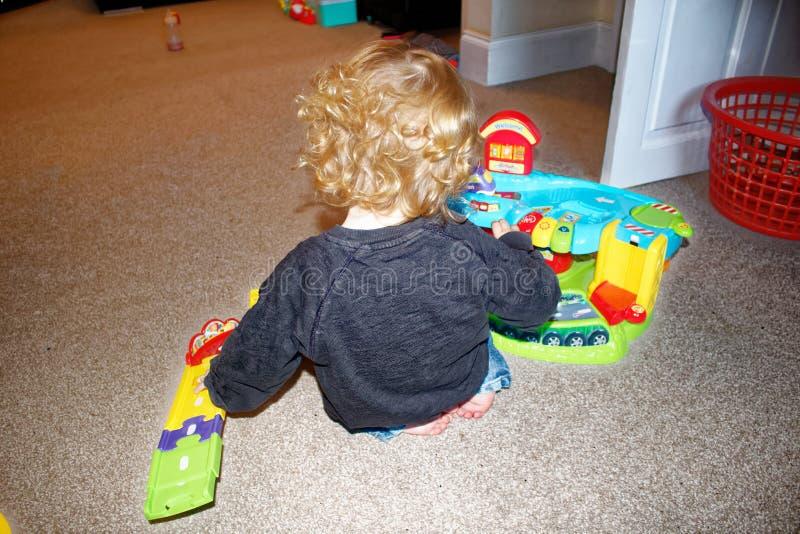 使用与玩具汽车和玩具车库的小孩 图库摄影