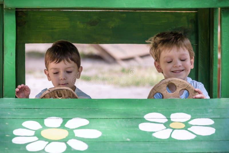 使用与玩具汽车的两个弟弟小孩在夏天从事园艺 有的男孩乐趣和好时间 在木在操场 免版税库存图片