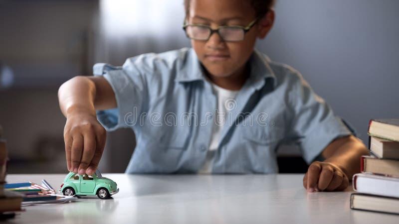 使用与玩具汽车的学龄前儿童男孩,作梦关于真正自动和旅行 免版税库存图片