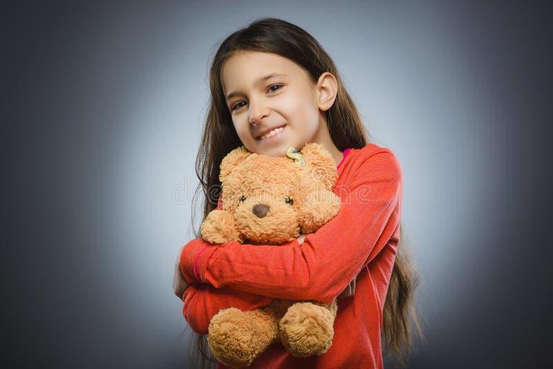 使用与玩具熊的愉快的女孩画象隔绝在灰色 免版税图库摄影