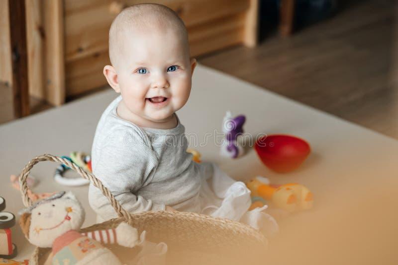使用与玩具的一个微笑的孩子的画象,当坐地板在席子的时托儿所 免版税库存照片