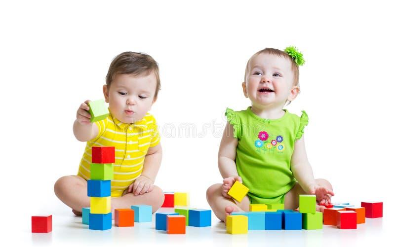 使用与玩具的两个可爱的孩子 小孩女孩 免版税库存图片