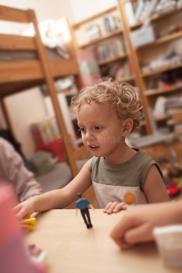 使用与玩具的小男孩在屋子里 免版税库存图片
