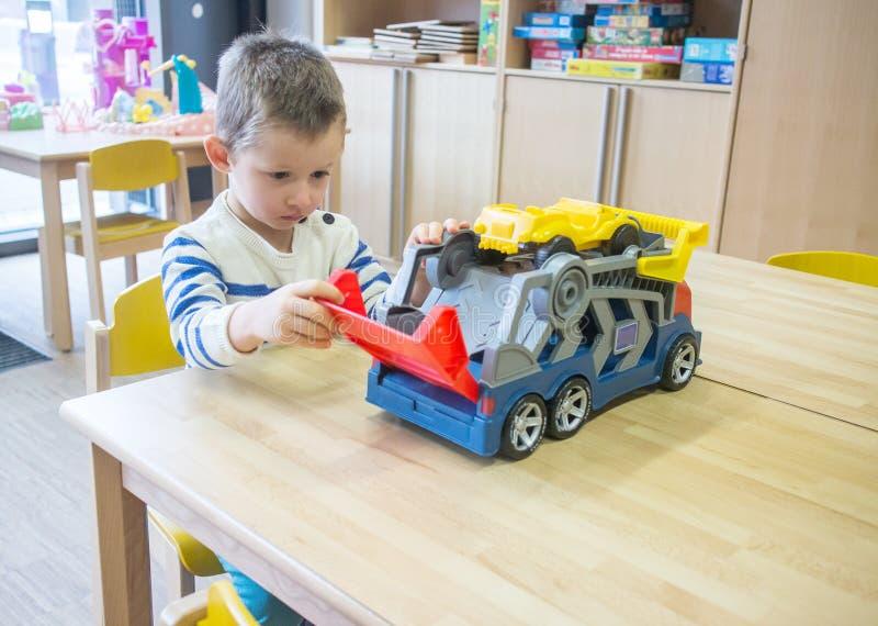 使用与玩具的男孩在幼儿园 免版税图库摄影