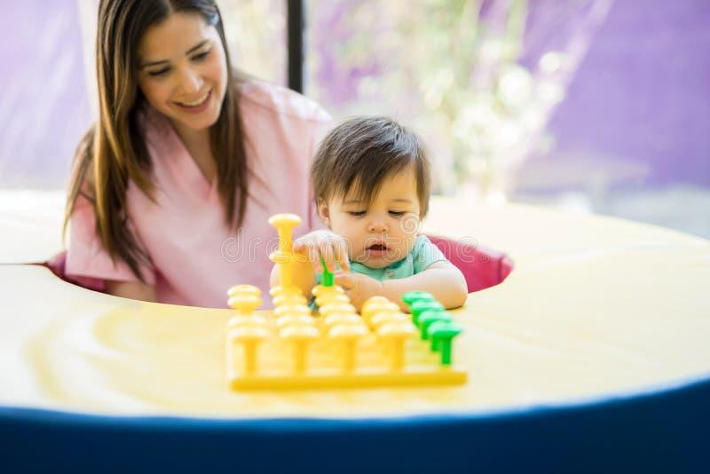 使用与玩具的婴孩和治疗师 免版税库存图片