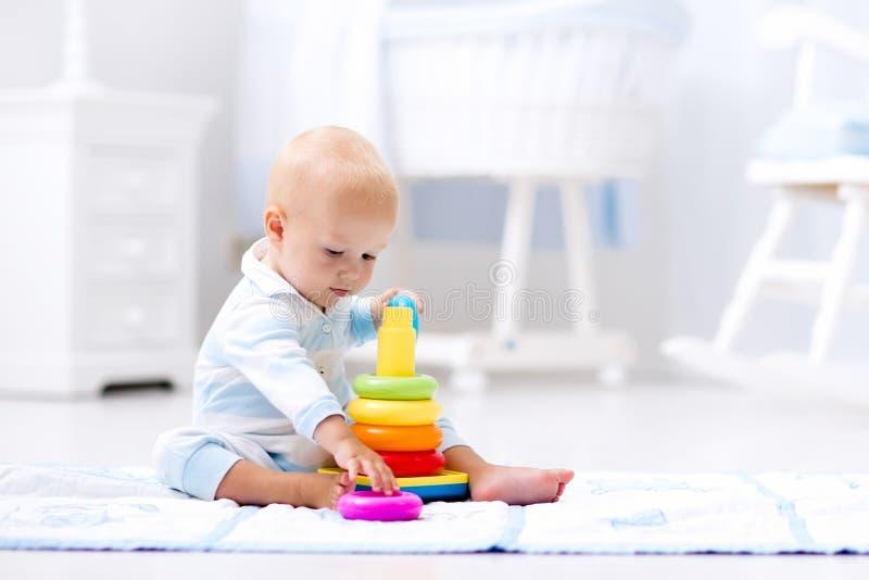 使用与玩具金字塔的婴孩 孩子戏剧 免版税图库摄影