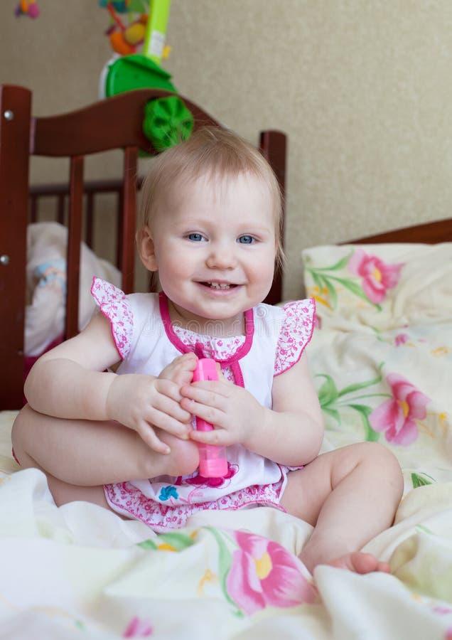 使用与玩具(标志)的可爱的白肤金发的女婴 免版税图库摄影