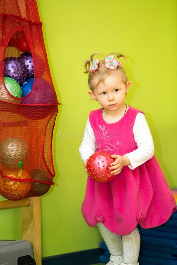 使用与球的小孩女孩在幼儿园在蒙台梭利类 免版税库存图片