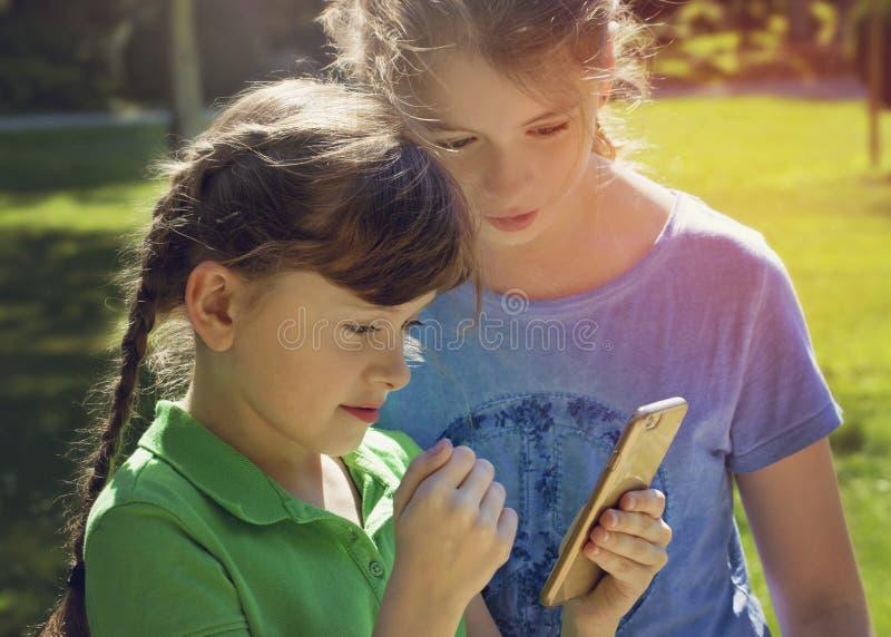 使用与电话的小女孩 免版税库存图片